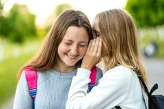 Two girl friends schoolgirls teenagers. In summer city park. Concept of joke, secret, fantasy, conversation, whisper. Surprise. Emotion of happiness is royalty free stock photography