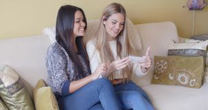 Two girl friends sending a text message. Two attractive young girl friends sending a text message on a mobile phone as they spend a relaxing day together at home stock footage