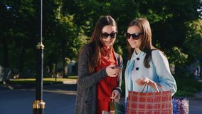 Two girl friends with shopping bags used smartphone outdoor. HD video stock video