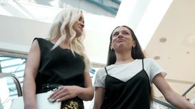 Two girl-friends on shopping has risen on the escalator with bags, fashion woman shopping stock video footage