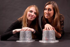 Two girl friends with silver hat Stock Images