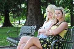 Two girl friends sitting on a bench Stock Photos