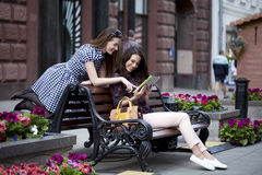Two girl friends sitting on a bench in the town center Royalty Free Stock Image
