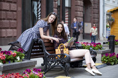 Two girl friends sitting on a bench in the town center Royalty Free Stock Images