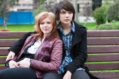 Two girl friends sitting on a park bench Stock Images