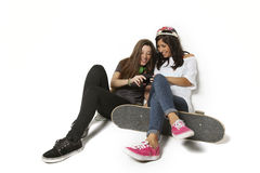 Two girl friends skateboarding looking on phone stock images