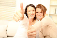 Two Girl Friends thinking positive. Two girl friends sitting together on the couch royalty free stock image