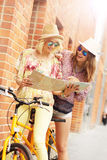 Two girl friends using map while riding tandem bicycle Stock Photography