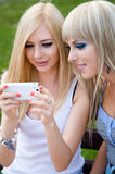 Two girl friends using a smartphone royalty free stock photography