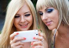 Two girl friends using a smartphone Royalty Free Stock Photos