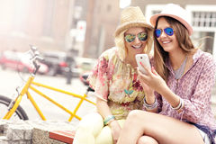 Two girl friends using smartphone while riding tandem bicycle Royalty Free Stock Image