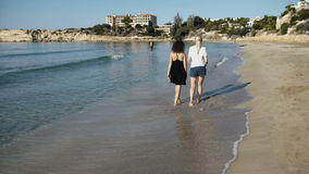 Two girl friends are walking along the beach near the ocean. Two beautiful girls are walking along the beach near the ocean. Shoots from the backs of females stock video footage