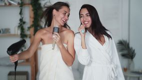 Two girl friends in white bathrobe dance, sing and dry hair with hairdryer, laugh