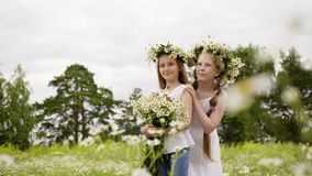 Two girl friends in wreath with flowers bouquet standing on blooming field. Teenager girls posing on flowering field at. Sunny summer day stock video