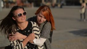 Two girl friends young female friends giving piggyback on vacation laughing and walking in the city, sunny day. Happy mood stock footage