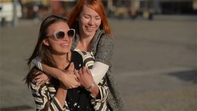 Two girl friends young female friends giving piggyback on vacation laughing and walking at the street, beautiful city stock footage