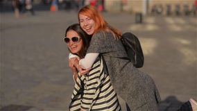 Two girl friends young female friends giving piggyback on vacation laughing and walking at the street, beautiful city