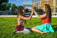 Two girl friends with zizi cornrows dreadlocks giving high five to each other Royalty Free Stock Photos