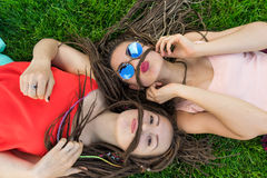 Two girl friends with zizi cornrows dreadlocks lying on green lawn Stock Images