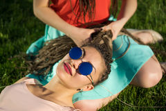 Two girl friends with zizi cornrows dreadlockson green lawn. Royalty Free Stock Photo