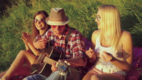 Two girl with funny boy rejoicing with guitar on the nature. 4k.  stock video