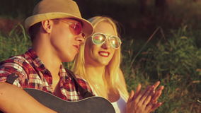 Two girl with funny boy rejoicing with guitar in the sunny park stock footage