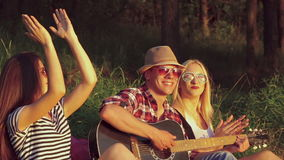 Two girl with funny boy rejoicing with guitar in the sunny park. Slow motion.  stock video