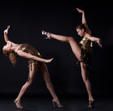 Two girl in gold dance costume posing with fight. Two girl in go-go gold dance costume posing in fight Stock Photos