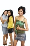 Two Girl Gossiping Behind Another Girl Back. Two Girls Are gossiping behind a girl back, shoot in white background. The two behind using cellphone to call their Royalty Free Stock Photography