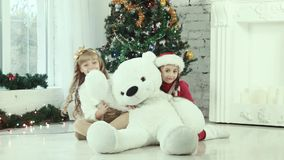 Two girl hiding behind the bear and smiling at the camera stock footage