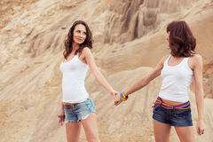 Two girl holding hands on beach Stock Images