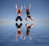 Two girl jumping to the water Royalty Free Stock Photography