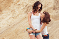 Two girl laughing and hugging on beach Stock Images