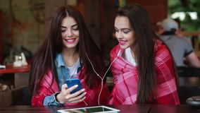 Two girl listening music with a smartphone. Two young and beautiful girl sitting at the table listening to music with a smartphone stock video footage