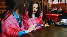 Two girl listening music with a smartphone. Two young and beautiful girl sitting at the table listening to music with a smartphone stock video
