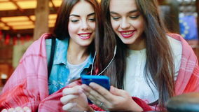 Two girl listening music with a smartphone. Two young and beautiful girl sitting at the table listening to music with a smartphone stock footage