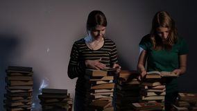 Two girl, mother and her teen daughter, or two sisters are reading books and having fun with books. 4K UHD. stock video footage