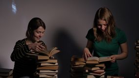 Two girl, mother and her teen daughter, or two sisters are reading books and having fun with books. 4K UHD. Two girl, mother and her teen daughter, or two stock video