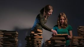Two girl, mother and her teen daughter, or two sisters are reading books and having fun with books. 4K UHD. stock footage