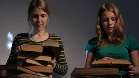 Two girl, mother and her teen daughter, or two sisters are reading books and having fun with books. 4K UHD. Two girl, mother and her teen daughter, or two stock video footage