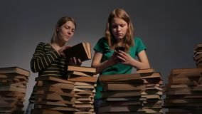 Two girl, mother and her teen daughter, or two sisters are reading books and having fun with books. 4K UHD. Two girl, mother and her teen daughter, or two stock footage