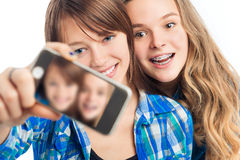 Two girl photographing themselves on a mobile phone. Stock Photography