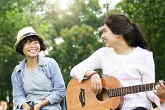 two girl playing guitar  and smile with happy in nature royalty free stock photos