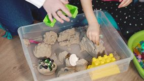 Two girl playing with kinetic sand at home stock video footage