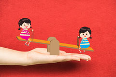 Two girl playing riding seesaw on hand Royalty Free Stock Photo