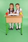 Two girl in a school uniform sitting at a desk and reading a book. Isolated on green Royalty Free Stock Image