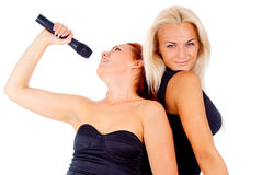 Two girl sing into the microphone. Isolated on white background Stock Images
