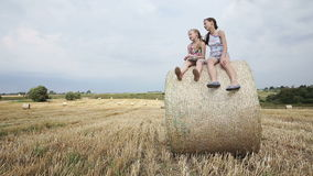 Two girl sits on haystack. Young happy children sitting on a hay bale in the field in the summer day,blue sky.Summer vacation stock footage
