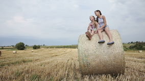 Two girl sits on haystack. Young happy children sitting on a hay bale in the field in the summer day,blue sky.Summer vacation stock video footage