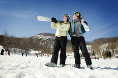 Two girl skiers pointing up towards sky Stock Photos